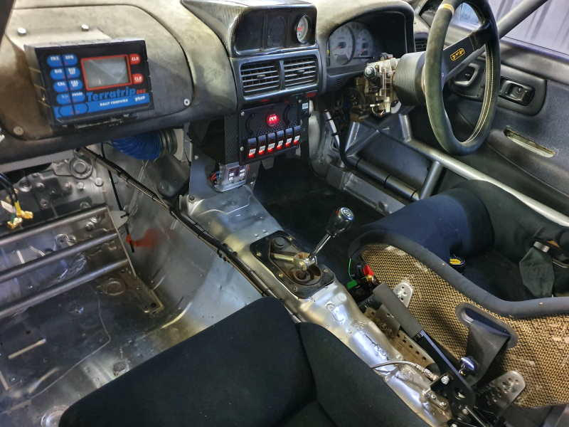 The interior of the Subaru WRX rally car showing switch panel and lines.