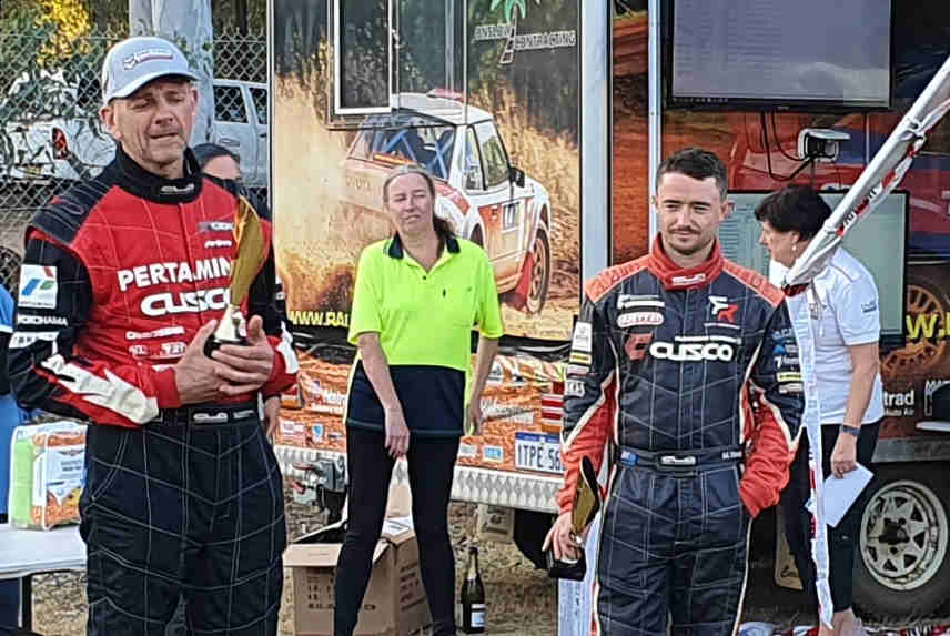Scott Beckwith makes a speech with driver Mike Young after winning the 2020 Safari Darling rally